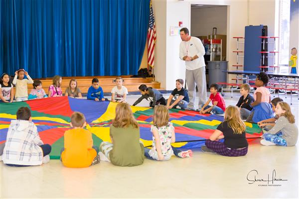 teacher instructing students with parachute activity