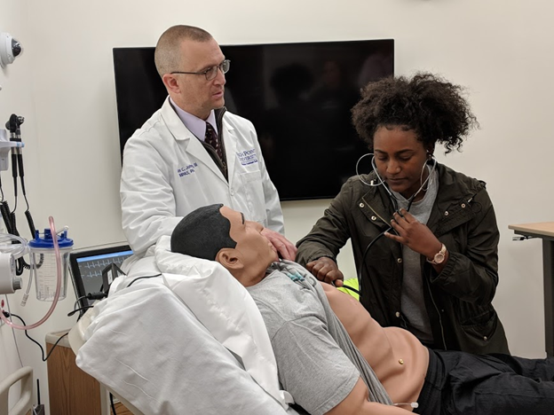 Student practicing listening for a heartbeat on a simulation manequin