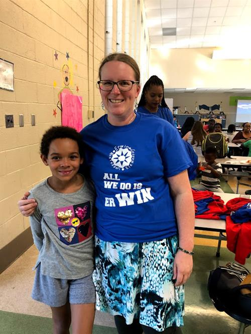 a pta member in an Erwin shirt stands next to an Erwin student in the cafeteria.