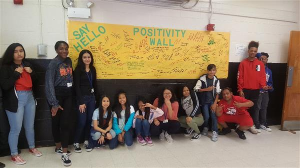 Welborn Celebrates Say Hello Week with students posing in front of signed Start with Hello Banner