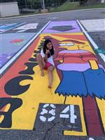 Image of student showing off her Simpson's parking space she painted.