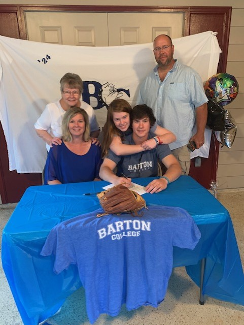 image of caleb and his family at table signing to attend Barton College