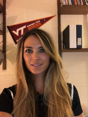 headshot photo of White female in front of VT flag