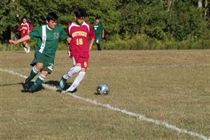 Two male soccer players trying to kick a soccer ball