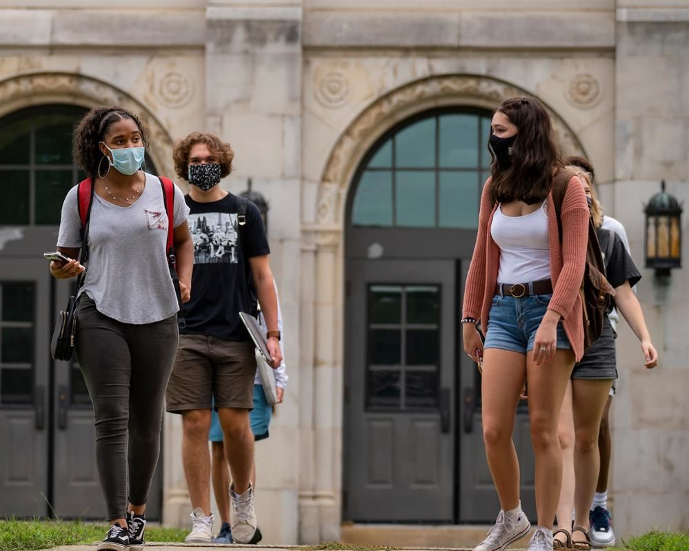 students walking on campus and social distancing wearing masks