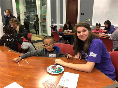 HPU Student and Fairview Scholar work on a holiday craft together.