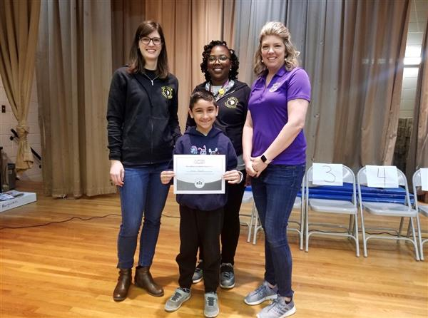 Staff Members Mrs. Sadlik, Mrs. Brown, and Ms. Baker stand with Fahad Ahmed Spelling Bee Champ!