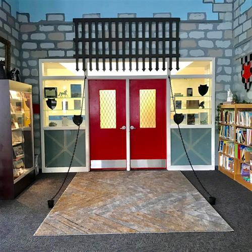 Drawbridge inspired red doors leading from library into hallway with bookcases