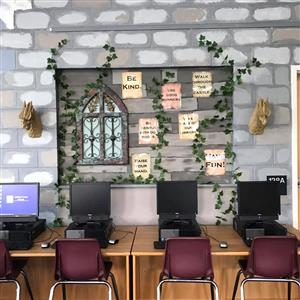 desks with computers below a wall displaying the rules and castle decorations