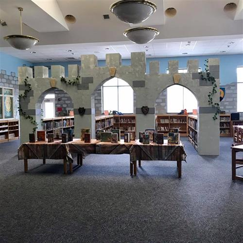 castle arches, bookcases, and table displaying books inside school library