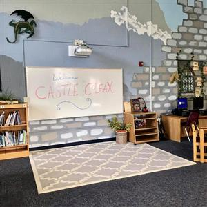 whiteboard that says Welcome to Castle Colfax, carpet, projector, dragon, bookcase, and desk with computers