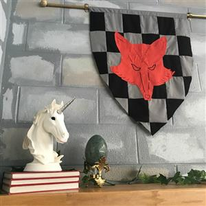 Unicorn statue on books beside egg statue and fox banner