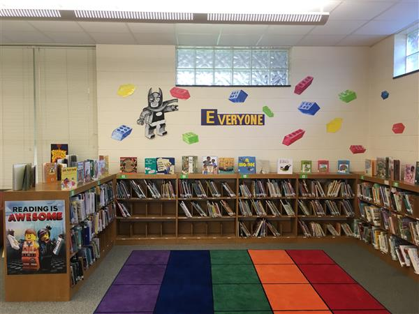 Photo of school library with lego decorations, a bookshelf, and a carpet.