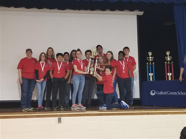 Students with red shirts holding trophy