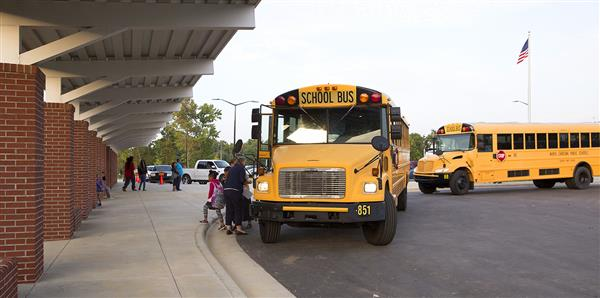 This is an image of two school busses pulling up to a school and letting students disembark.
