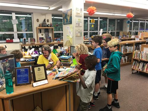 librarian with children at busy circulation desk