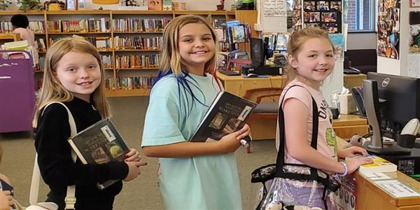 girls checking out books