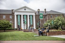 picture of greensboro college with students laughing in front of the main building