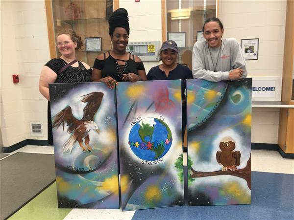 Artists pose with  mural at Reedy Fork Elementary