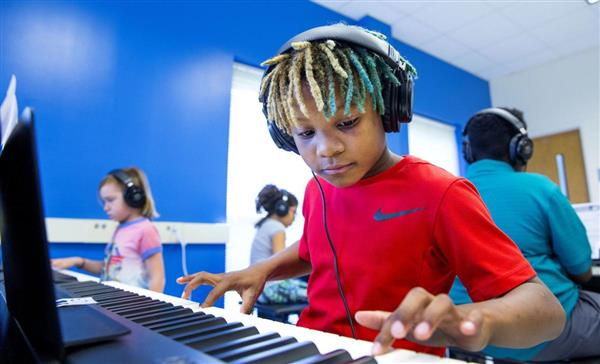 Student enjoys playing music on piano.