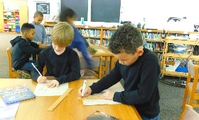 Two students working at a table with paper, pencils and rulers.