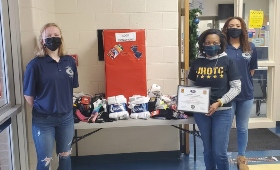 Photo of Mrs. McHam with Victoria Harper, and Isabella Munga from Grimsley's JROTC with socks