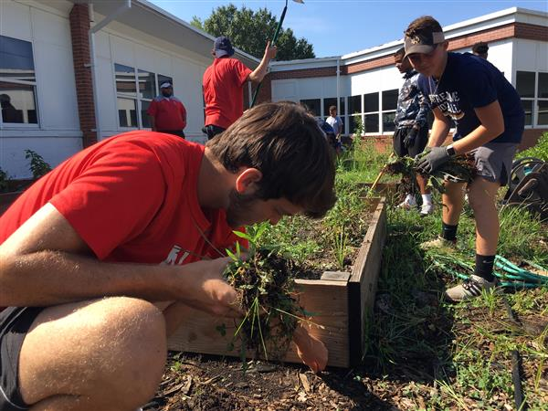 Football players work in Jones Elementary gardens