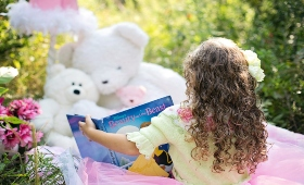 Girl reading to teddy bears