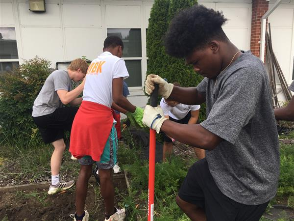 Football players work in Jones Elementary garden