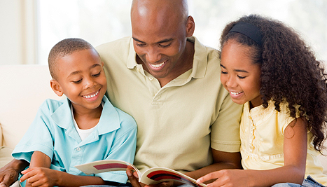 dad with kids reading a book