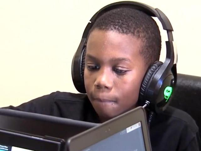 Student on computer with headphones