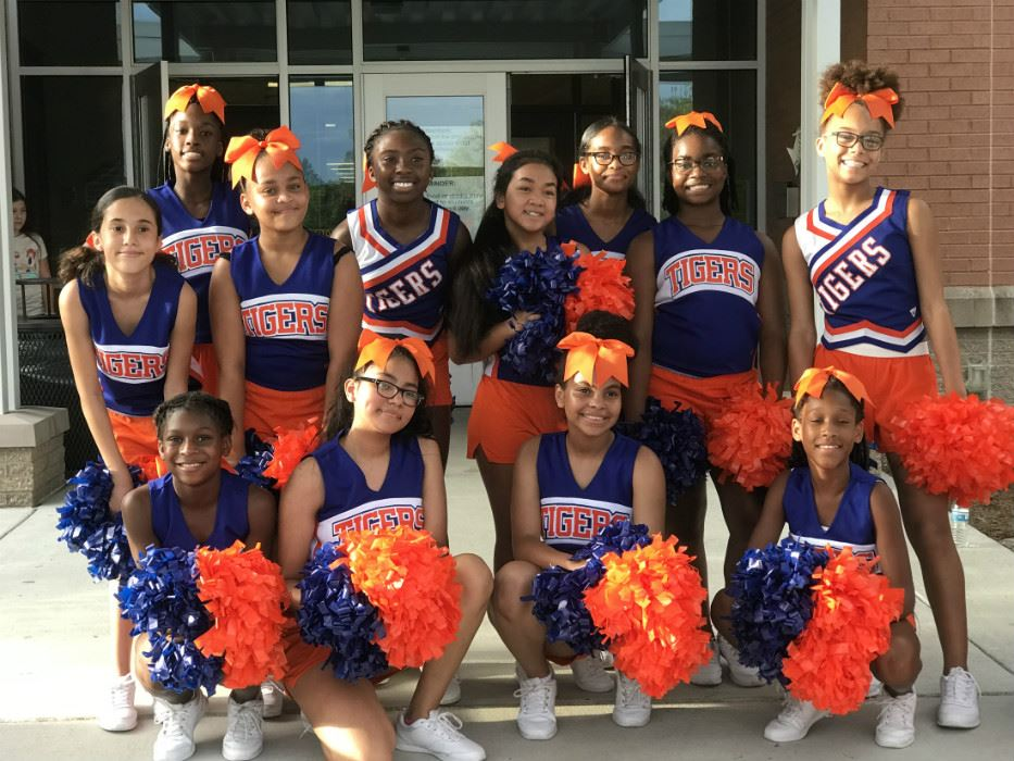 12 cheerleaders in JMS cheerleading outfits with pom poms.